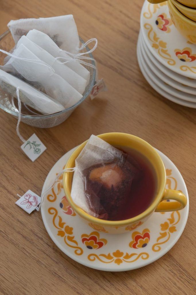 Xícara de chá com saquinho e bebida.