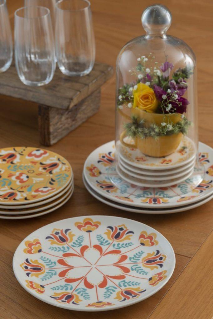 Pratos estampados com motivos florais estilizados e um arranjo de flores dentro de uma redoma de vidro