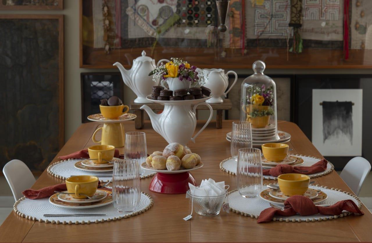 Mesa posta para o chá da tarde com louças em tons de amarelo, laranja e branco.