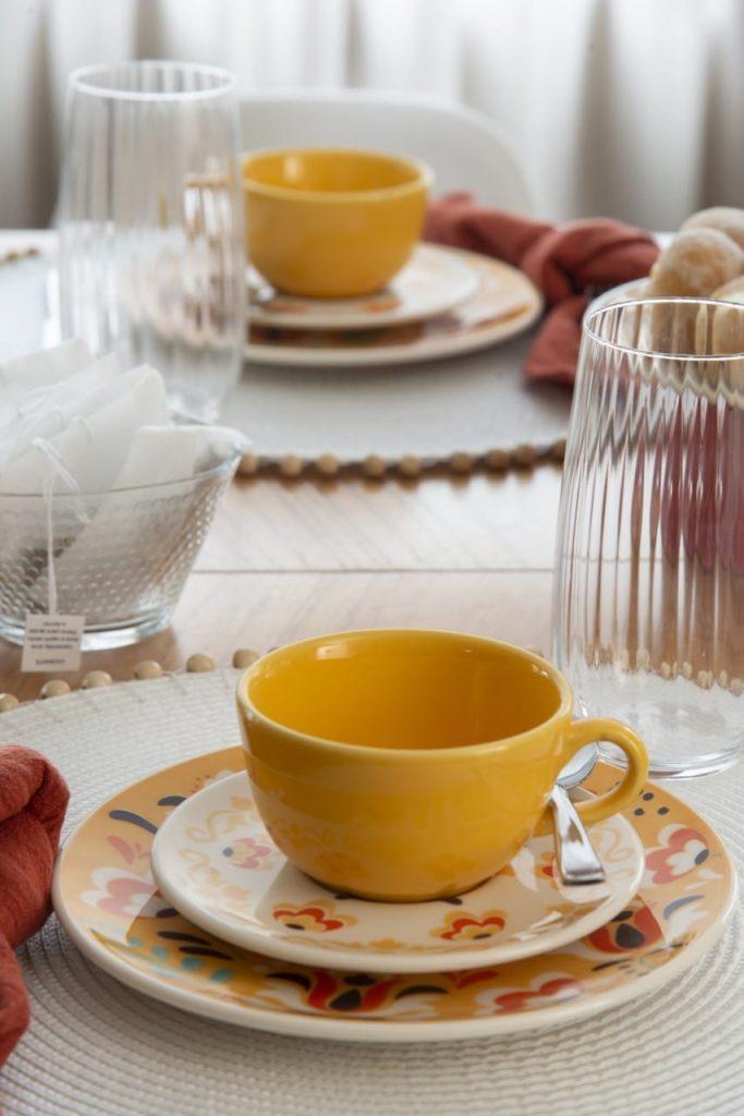Xícara amarela sobre pires branco e prato de sobremesa amarelo, ambos estampados.