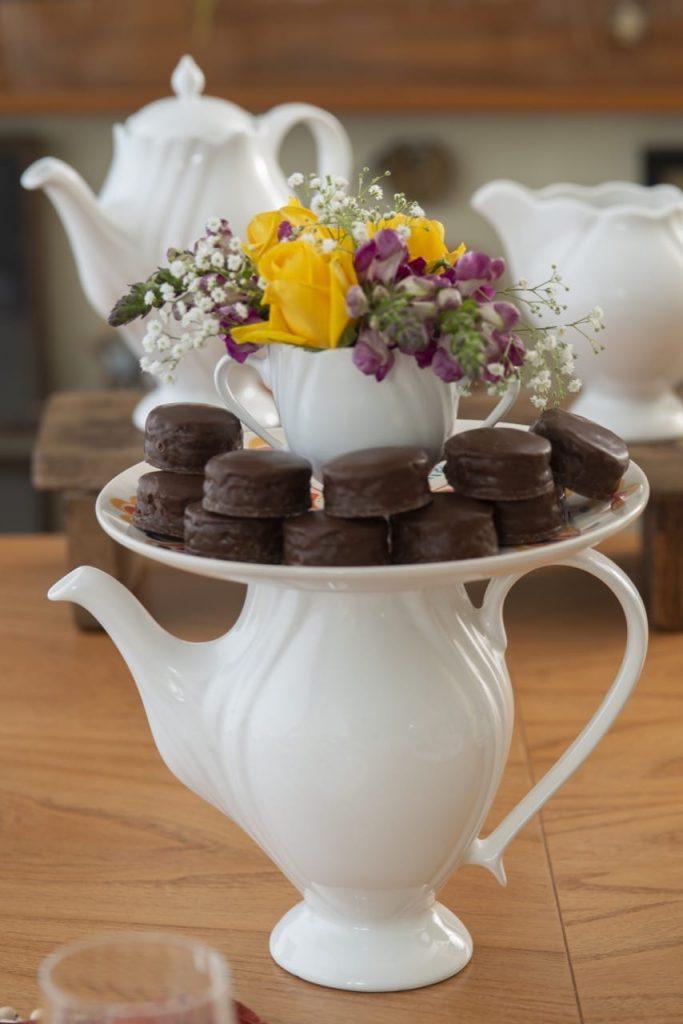 Bule branco com estilo romântico, prato com pães de mel e açucareiro com flores.