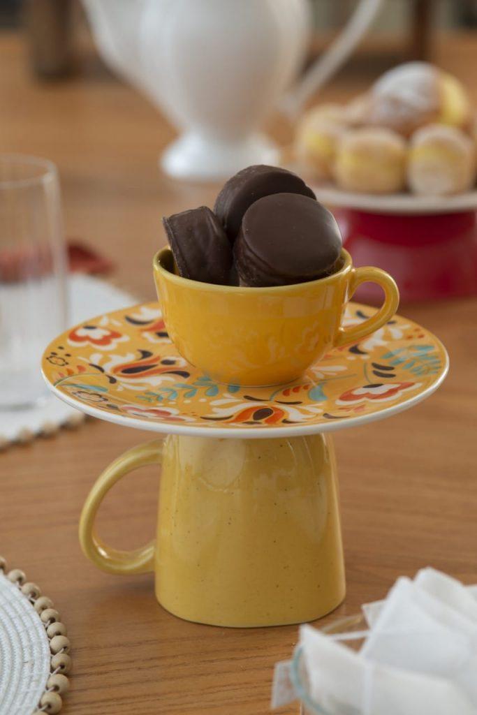 Xícara amarela contendo pães doces está sobre um prato de sobremesa apoiado numa caneca com a boca virada para baixo.