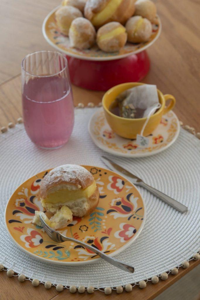 No prato de sobremesa, temos parte de um sonho. Ao lado, xícara com chá e copo com limonada rosa.