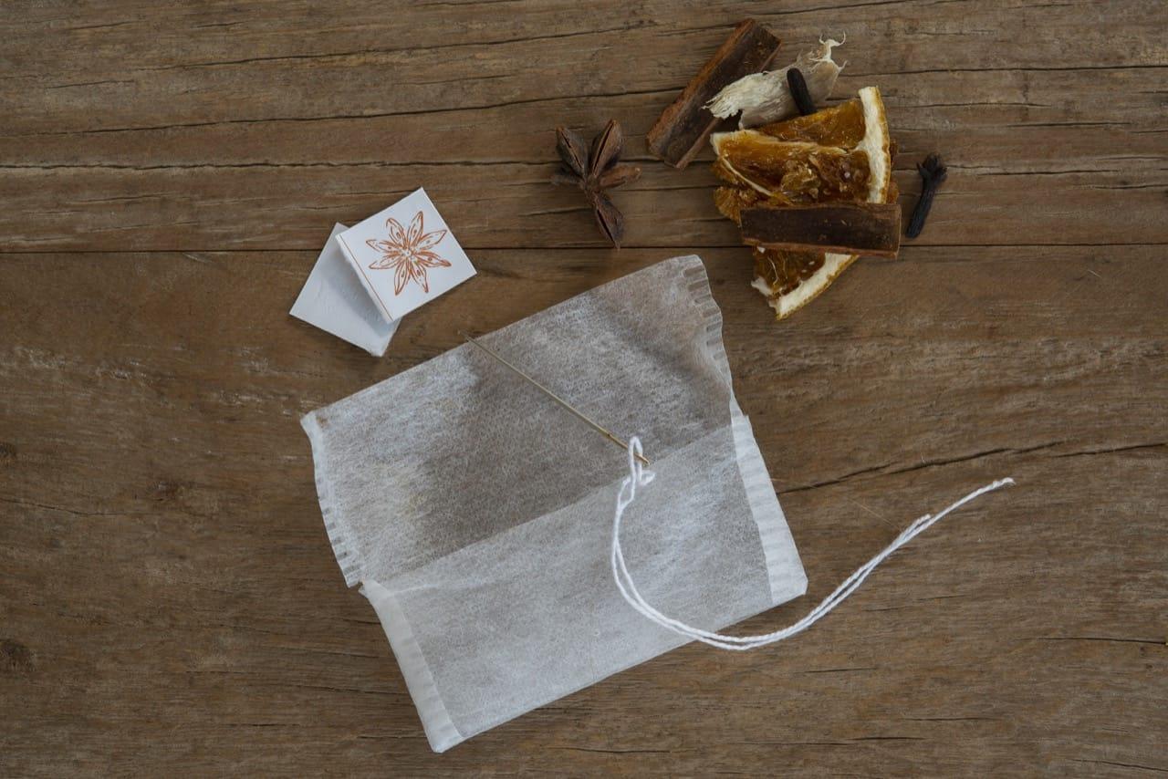 Saquinho de chá, etiquetas de papel, linha, agulha de costura e ingredientes para o chá (laranja desidratada, anis-estrelado, canela em pau e cravo)