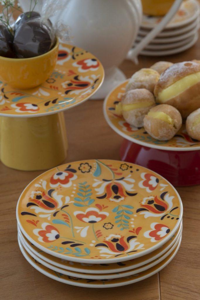 Na mesa polonesa, temos uma pilha de pratos amarelos com estampa de flores estilizadas em branco, laranja e marrom.