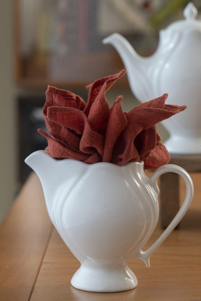 Leiteira branca contendo guardanapos vermelhos de tecido, enfeitam a mesa polonesa.