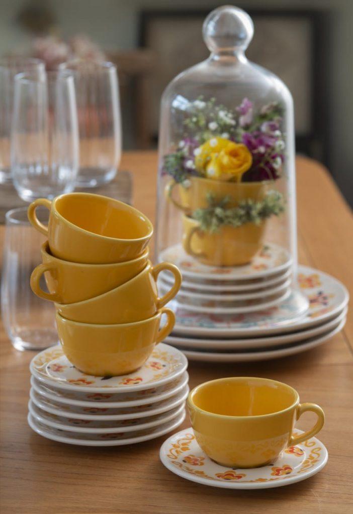 Pilha de xícaras amarelas sobre pires brancos estampados. Ao fundo há um arranjo floral dentro de uma redoma de vidro.