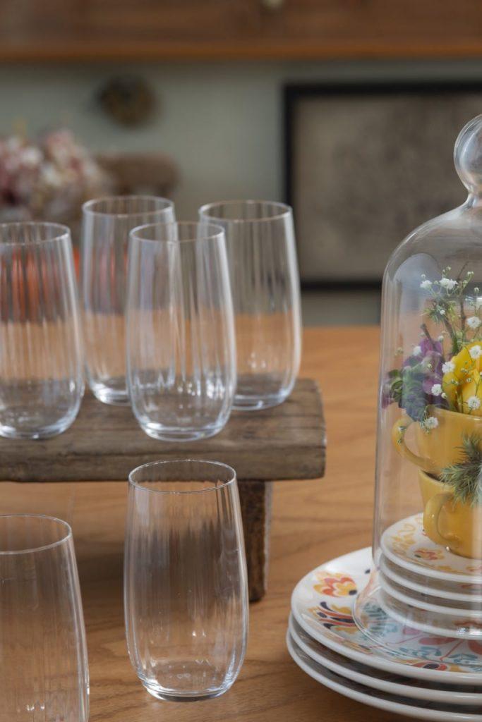 Quatro copos altos sobre um banquinho de madeira que está sobre a mesa. E dois copos na mesa.